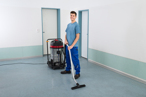 Male Worker With Vacuum Cleaner