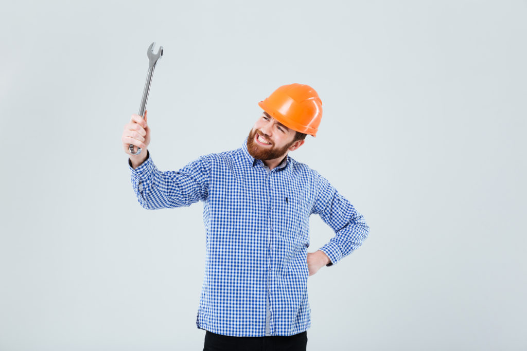 Cheerful bearded man in helmet holding and looking at wrench